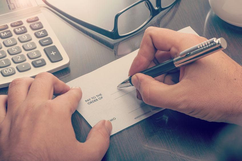 business executive writing a payroll check