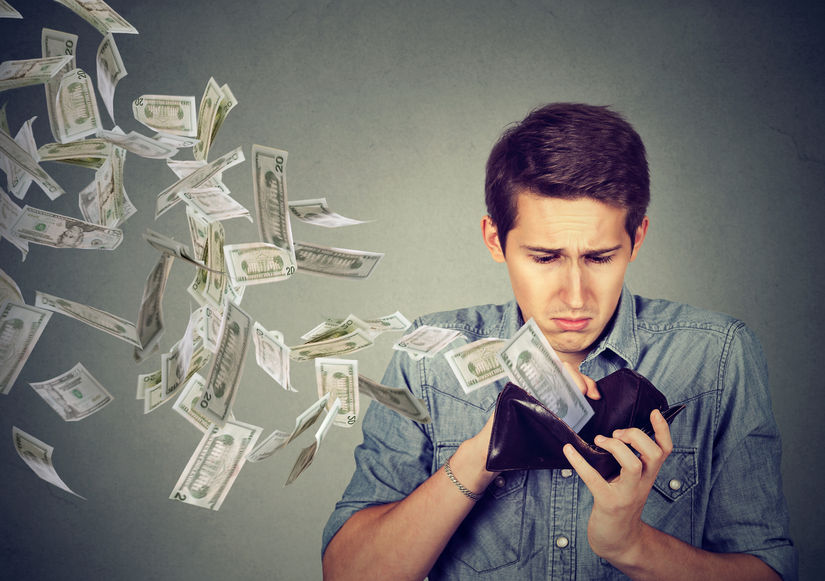sad man looking at his wallet with money flying away due to high health coverage costs