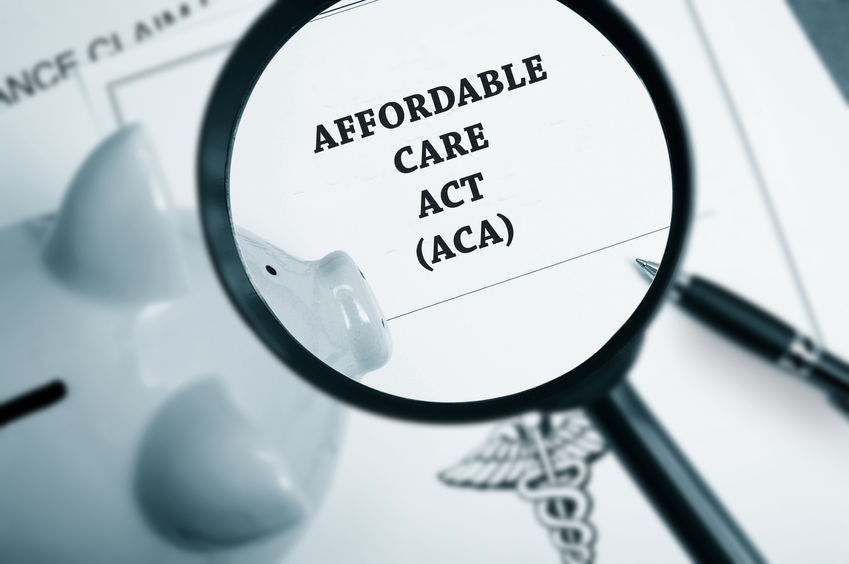 Magnifying glass over Affordable Care Act policy and business paperwork