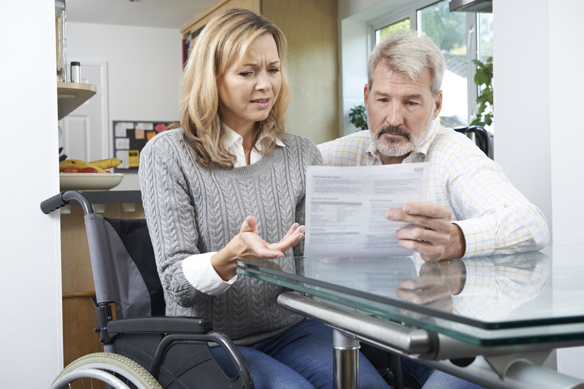 Frustrated Couple With Woman In Wheelchair Reading Insurance Bill