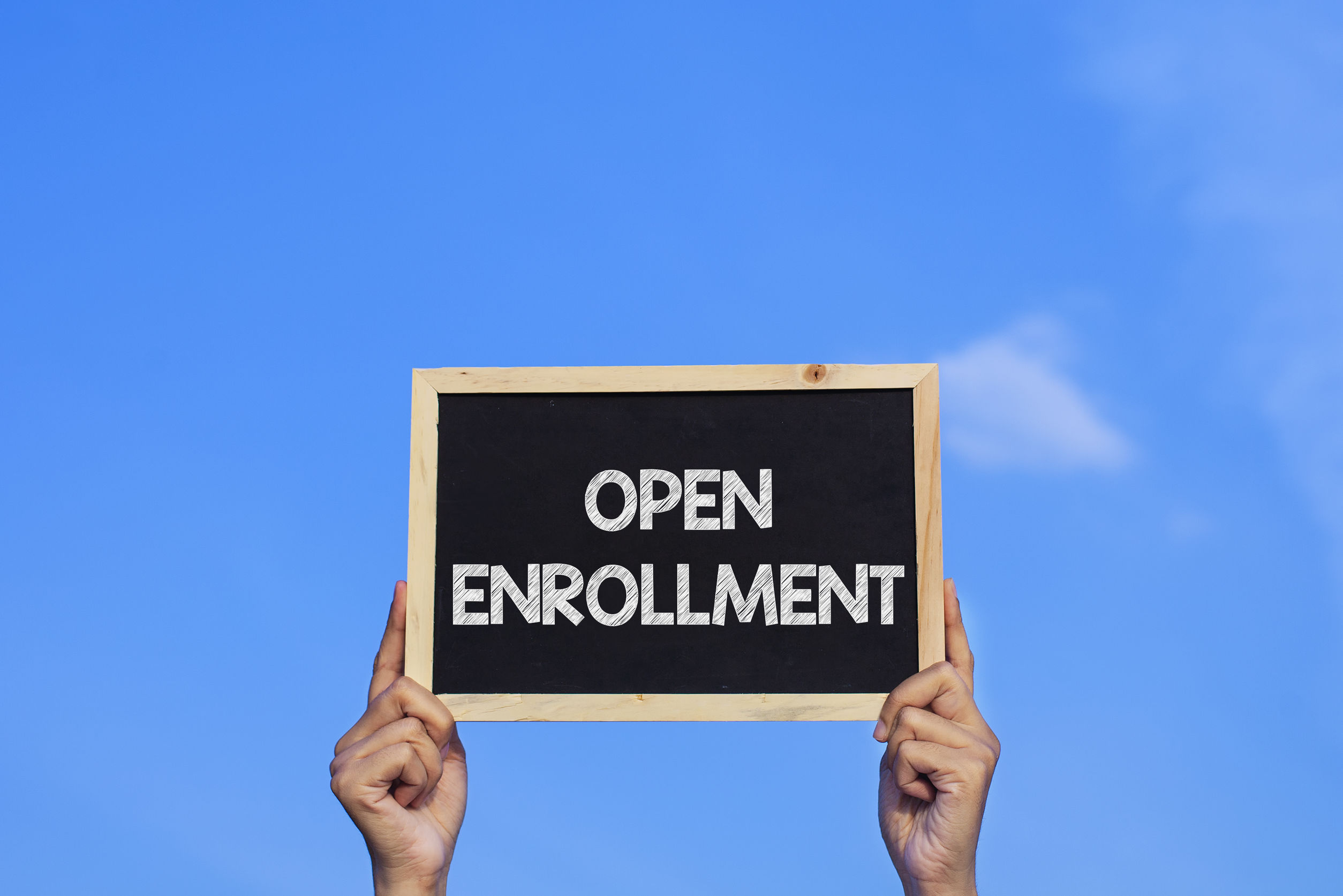 OPEN ENROLLMENT/ Man holding small blackboard on blue sky backgr